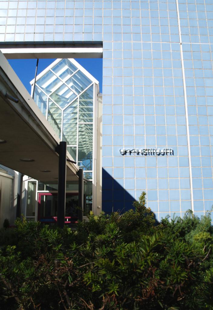 UKK-instituutin ulkoseinän logo ja pihan kasvillisuutta