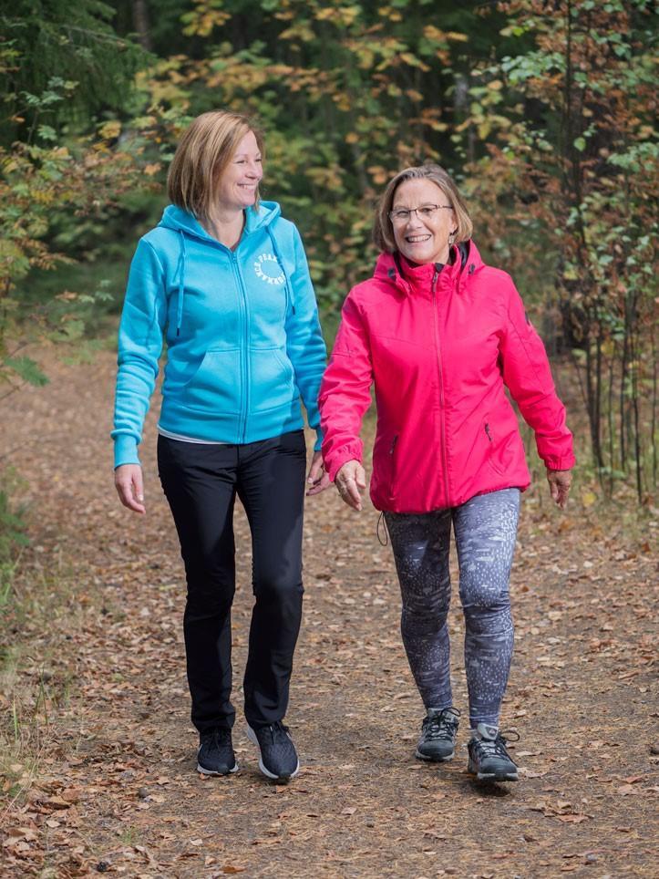 Kaksi hymyilevää naista Kaupinpuiston ulkoilureitillä
