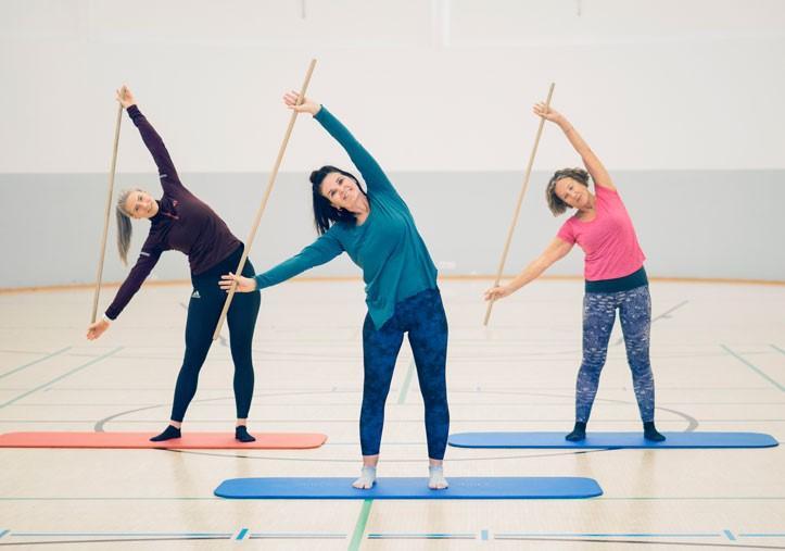 Kolme hymyilevää naista jumppaa kepin kanssa UKK-instituutin liikuntasalissa