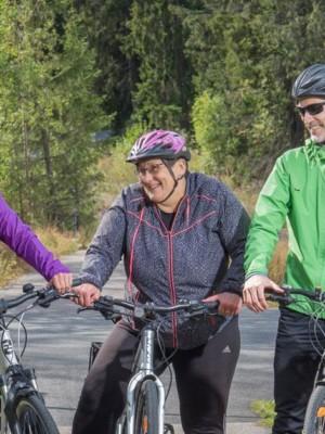 Kaksi naista ja yksi mies seisovat ryhmässä pyörien kanssa pyörätiellä.