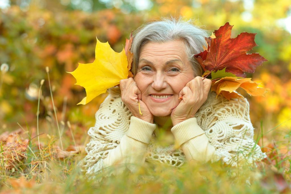 Iäkäs rouva on päinmakuulla nurmikolla ja nojaa käsiinsä, hymyilee ja pitää käsissään ruskan värisiä vaahteran lehtiä.