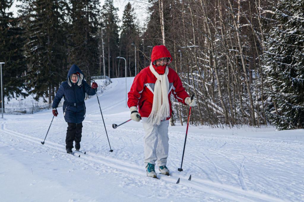 Kaksi iäkästä, hymyilevää naista hiihtämässä.