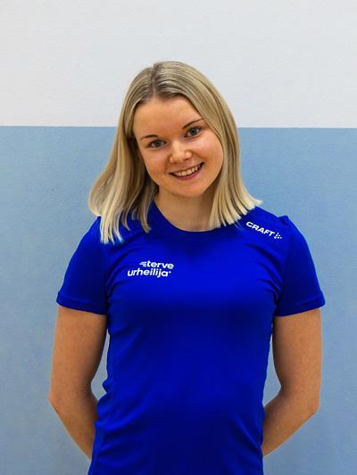 Lähikuva Iida Mustakoskesta sinisessä Terve urheilija -paidassa liikuntasalissa.